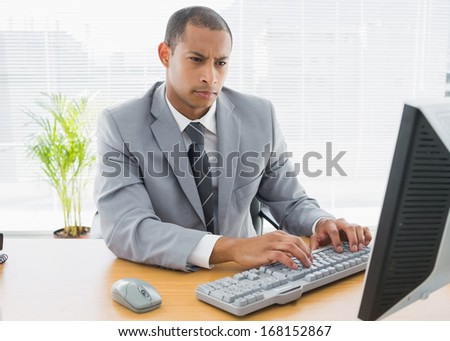 Concentrated young businessman using computer at office desk