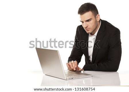 concentrated young businessman working on his laptop - stock photo