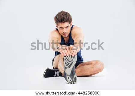 Concentrated young male athlete sitting on the floor and stretching legs over white background