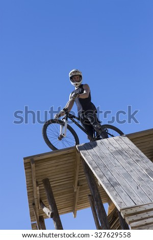 concentrated young man BMX bicycle rider is ready to jump on a wooden ramp on a BMX session in the mountain - focus on the face - stock photo