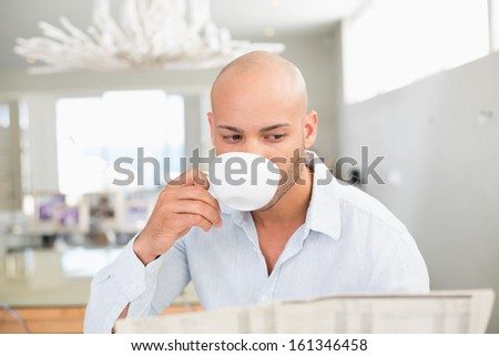 Concentrated young man drinking coffee while reading newspaper at home