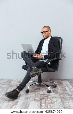 Concentrated young man in glasses sitting in office chair and using laptop - stock photo