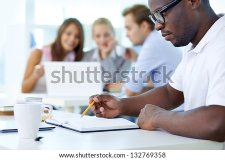 Concentrated young man in the foreground planning his workday - stock photo