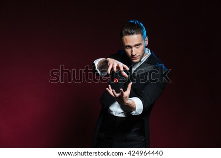 Concentrated young man magician conjuring tricks with red dice  over dark background - stock photo