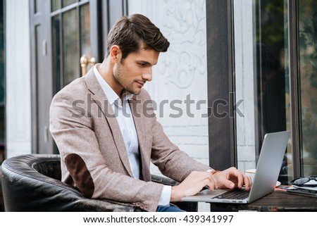 Concentrated young man sitting and using laptop in outdoor cafe