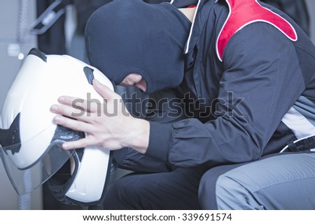 concentrated young man sitting on the locker room holding his helmet before starting a race in an outdoor go karting circuit - focus on the eye - stock photo