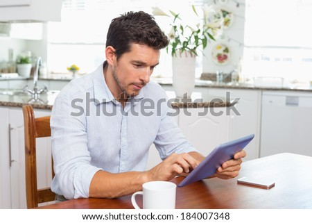 Concentrated young man using digital tablet in the kitchen at home - stock photo