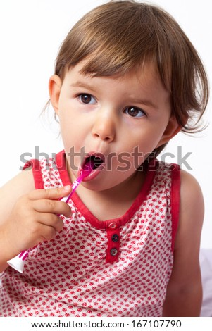 concentrated young toddler brushing her teeth