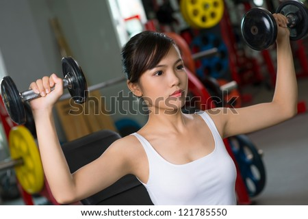 Concentrated young woman exercising with dumbbells - stock photo