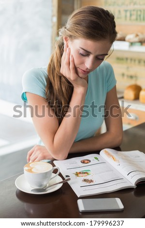Concentrated young woman with coffee cup reading magazine at counter in the coffee shop