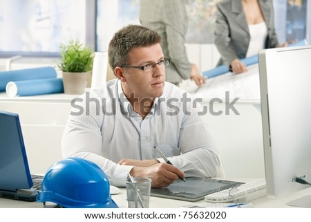 Concentrating architect at work, sitting at desk using drawing pad.? - stock photo