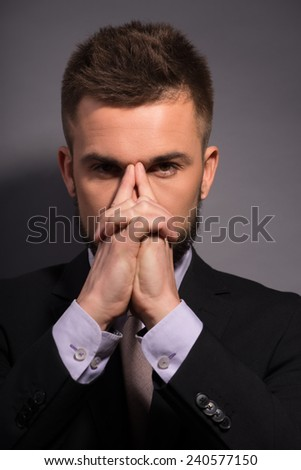 Concentrating at. Serious young bearded businessman in suit holding fingers on nose bridge while standing against grey background - stock photo