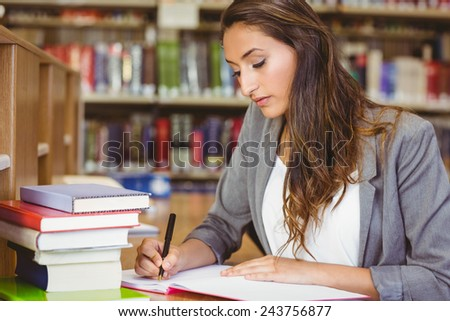 Concentrating brunette student doing her assignment in library