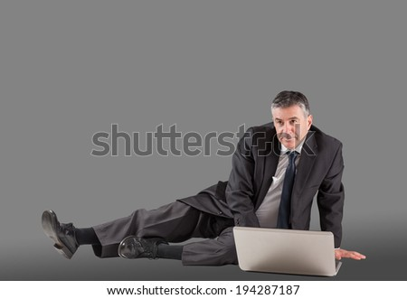 Concentrating businessman lying on floor using laptop on grey background