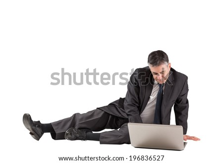 Concentrating businessman lying on floor using laptop on white background