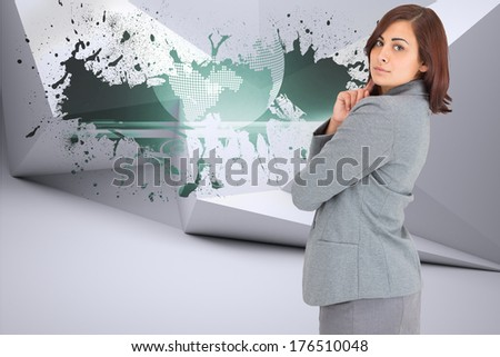 Concentrating businesswoman against splash on wall revealing global graphic - stock photo