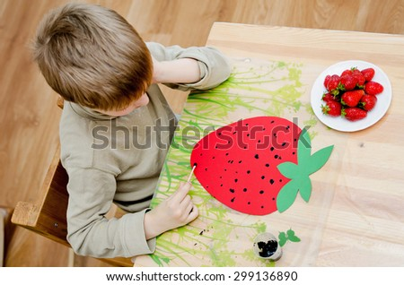 Concentrating child draws strawberry - stock photo