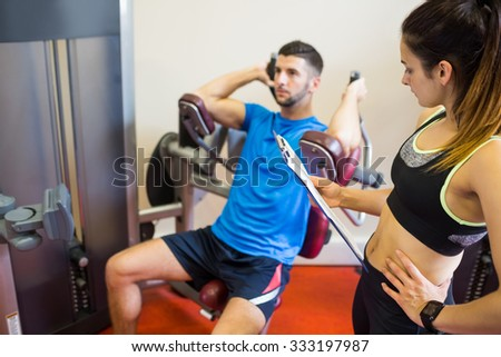 Concentrating man using weights machine with trainer at the gym