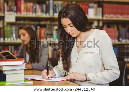 Concentrating pretty brunette student writing in notepad in library