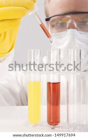 Concentrating to Drop Sample into Test Tube with Pipette - stock photo