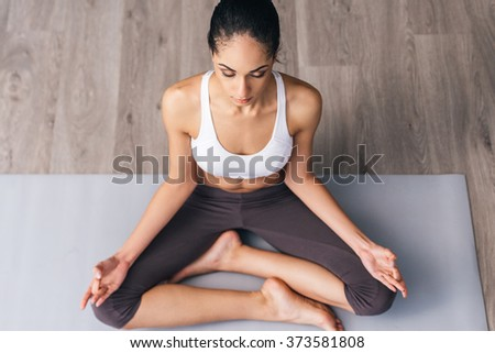 Concentration and meditation. Top view of beautiful young African woman in sportswear practicing yoga while sitting in lotus position on the floor - stock photo