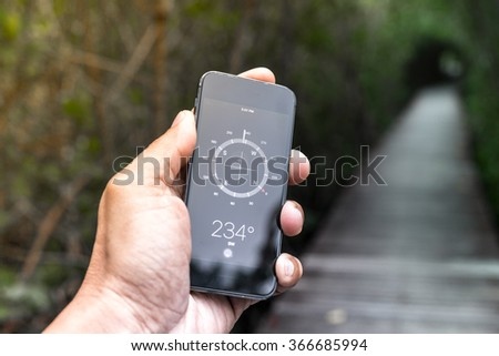 Concept a Hand Holding a Compass on smart phone in jungle background - stock photo
