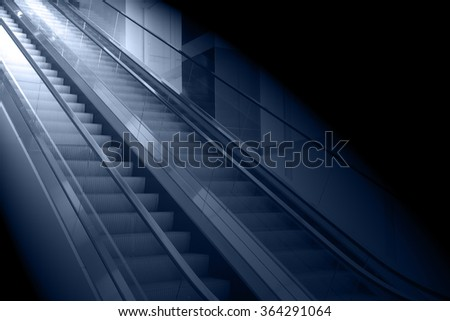 concept background of escalator with the light at the end - stock photo