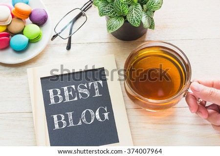 Concept BEST BLOG message on wood boards. Macaroons and glass Tea on table. Vintage tone. - stock photo
