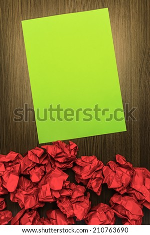 Concept brilliant or good idea, better than the rest. With highlighted green paper and red crumpled wastepaper. - stock photo