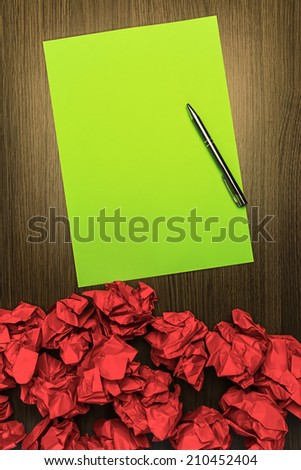 Concept brilliant or good idea, better than the rest. With highlighted green paper, red crumpled wastepaper and pen. - stock photo