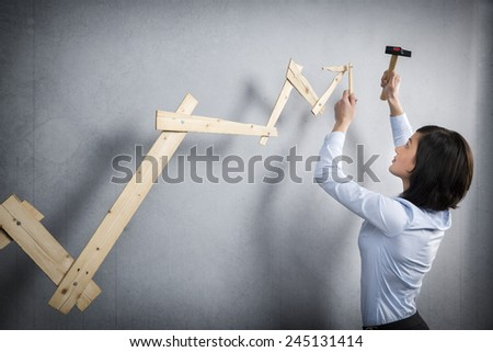 Concept: Building your own career or business. Young businesswoman installing upward arrow on floating business graph with positive trend, isolated on grey background - stock photo