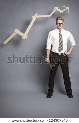 Concept: Building your own successful career or business. Young confident businessman holding  wrench in front of business graph with positive trend, isolated on grey background. - stock photo