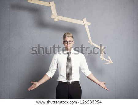 Concept: Business decline. Young displeased businessman in front of business graph pointing down, isolated on grey background. - stock photo