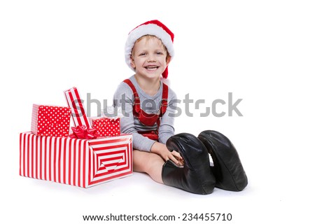 Concept: Christmas in childhood. Kid in red costume of dwarf with gifts. Studio portrait isolated over white background   - stock photo