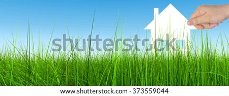 Concept conceptual white paper house held in hand by a man in a green summer grass over a blue sky background with clouds banner a symbol for construction, eco, ecology, loan, mortgage, property home - stock photo