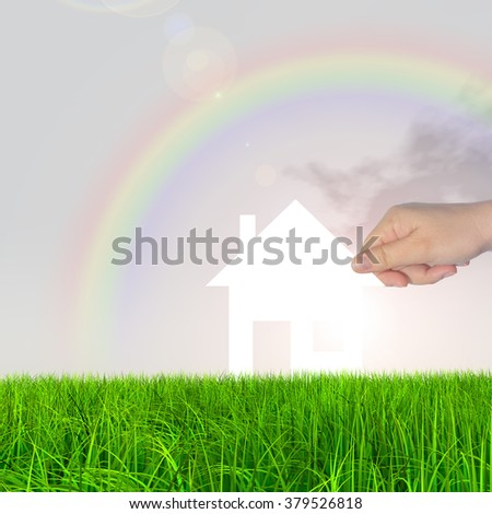 Concept conceptual white paper house held in hand by a man in a green summer grass over a rainbow sky background with clouds, a symbol for construction, eco, ecology, loan, mortgage, property or home - stock photo