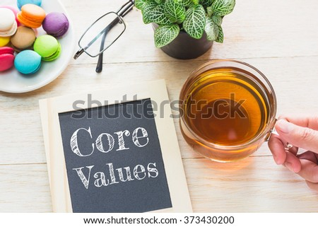 Concept Core Values message on wood boards. Macaroons and glass Tea on table. Vintage tone. - stock photo