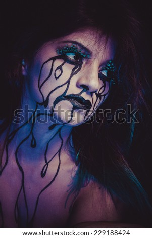 concept, crying woman with tears and makeup dark light - stock photo