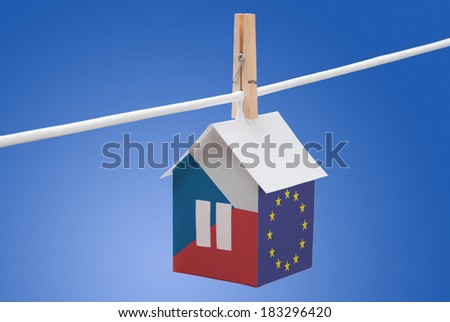 concept - Czech and EU flag painted on a paper house hanging on a rope - stock photo