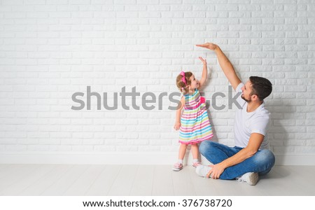 concept. Dad measures the growth of her child daughter at a blank brick wall - stock photo
