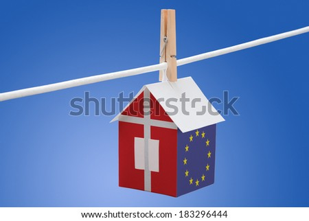 concept - Denmark and EU flag painted on a paper house hanging on a rope - stock photo