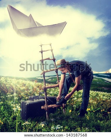 Concept - dreaming about travel.Handsome man with suitcases standing near the ladder to the flying paper boat in the clouds - stock photo