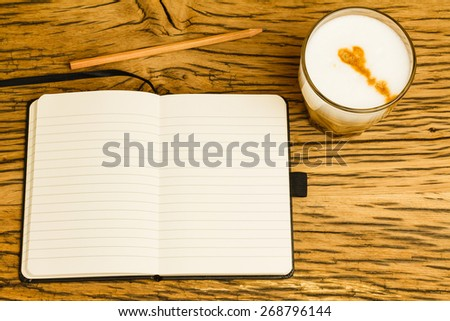 Concept empty notebook with pencil, start of the day. Coffee on oak desk. - stock photo