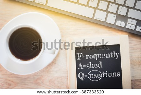 Concept FAQ message on wood boards. A keyboard and a glass coffee table.Vintage tone. - stock photo