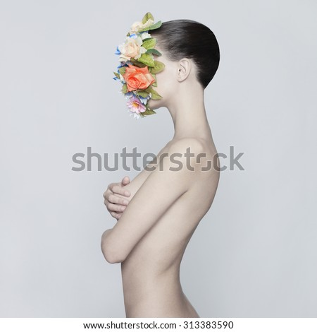 Concept fashion studio portrait of nude elegant lady with flower on her face - stock photo