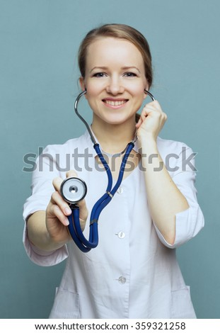 Concept: focus on the stethoscope. Doctor holding a stethoscope. Medical doctor woman with stethoscope white lab coat and glasses on a blue background smiling