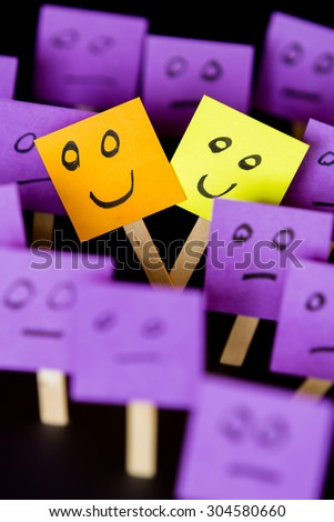 Concept for being different and being happy in a word of normal, hand drawn faces on sticky notes over a black background - stock photo