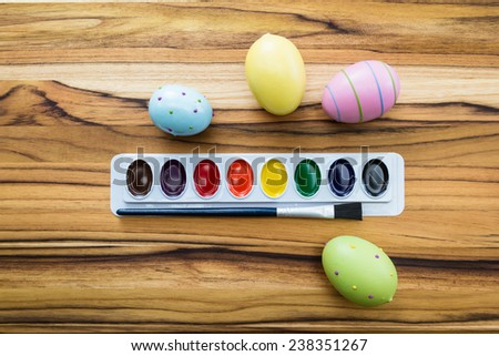 concept for easter eggs with pastel colors and paint brushes on a wooden table
