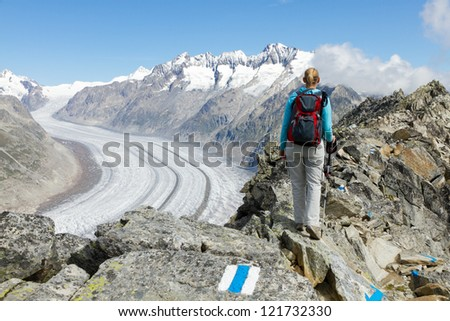 concept for hiking, climbing, walking and outdoor adventures: woman on mountain top with backpack and sticks above Aletsch glacier Switzerland - stock photo