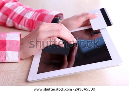Concept for Internet shopping: hands holding tablet and credit card - stock photo